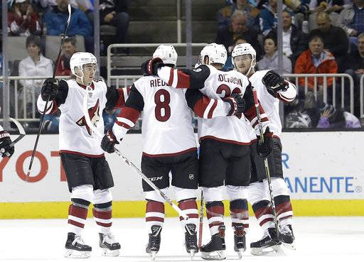 Arizona Coyotes defenseman Alex Goligoski, second from right, celebrates with teammates after scoring a goal against the San Jose Sharks during the second period of an NHL hockey game in San Jose, Calif., Tuesday, Feb. 13, 2018.