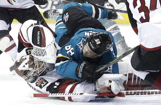 San Jose Sharks right wing Melker Karlsson, from Sweden, top, crashes into Arizona Coyotes goaltender Scott Wedgewood during the second period of an NHL hockey game in San Jose, Calif., Tuesday, Feb. 13, 2018.