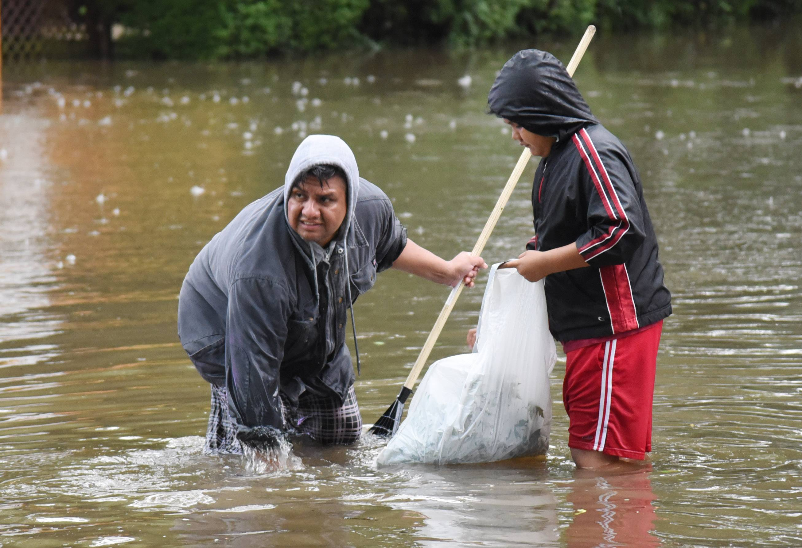 Jorge Morales and his son, Ariel, try to clear street drains in Mundelein during the July 2017 flood.