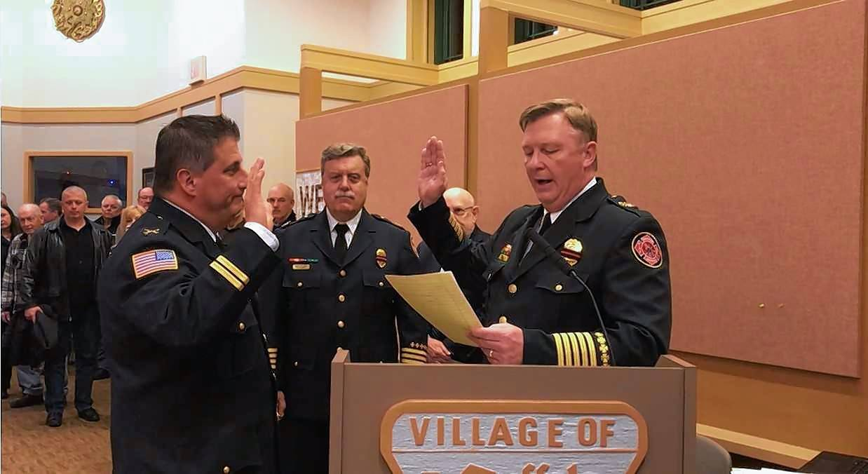 Newly promoted Buffalo Grove Fire Department Batallion Chief Joe Alexander, left, is sworn in at a recent village board meeting by Chief Mike Baker, as Deputy Chief William Wagner looks on.