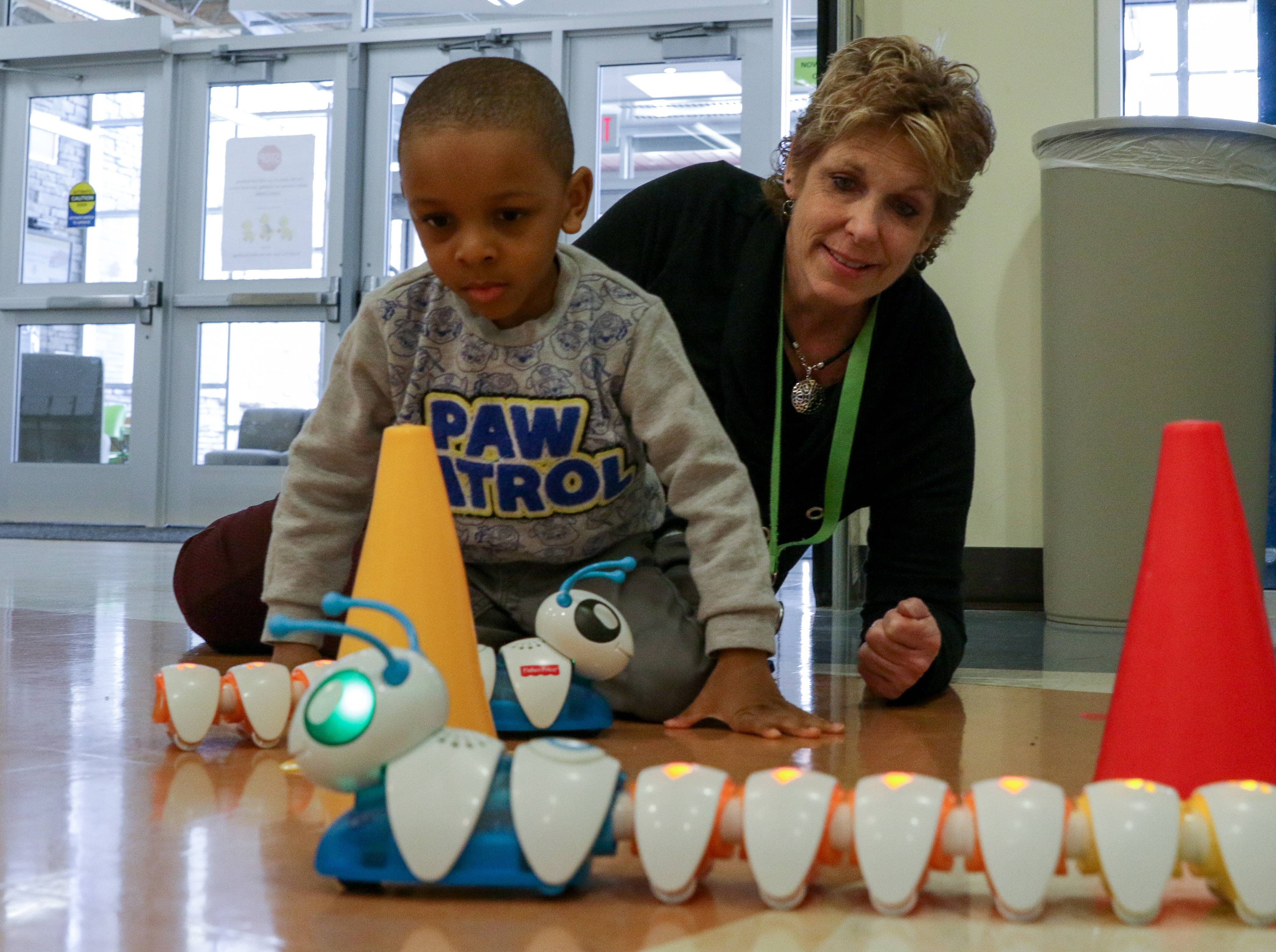 Assistant teacher Dawn Enright works with Javion Stevens, 4, as preschoolers at the Ann Reid Early Childhood Center in Naperville Unit District 203 experience an Hour of Code with computer coding basics. Javion was working with an educational toy called the Code-a-pillar, attaching pieces with different arrows to direct it to move in a circle around a cone.