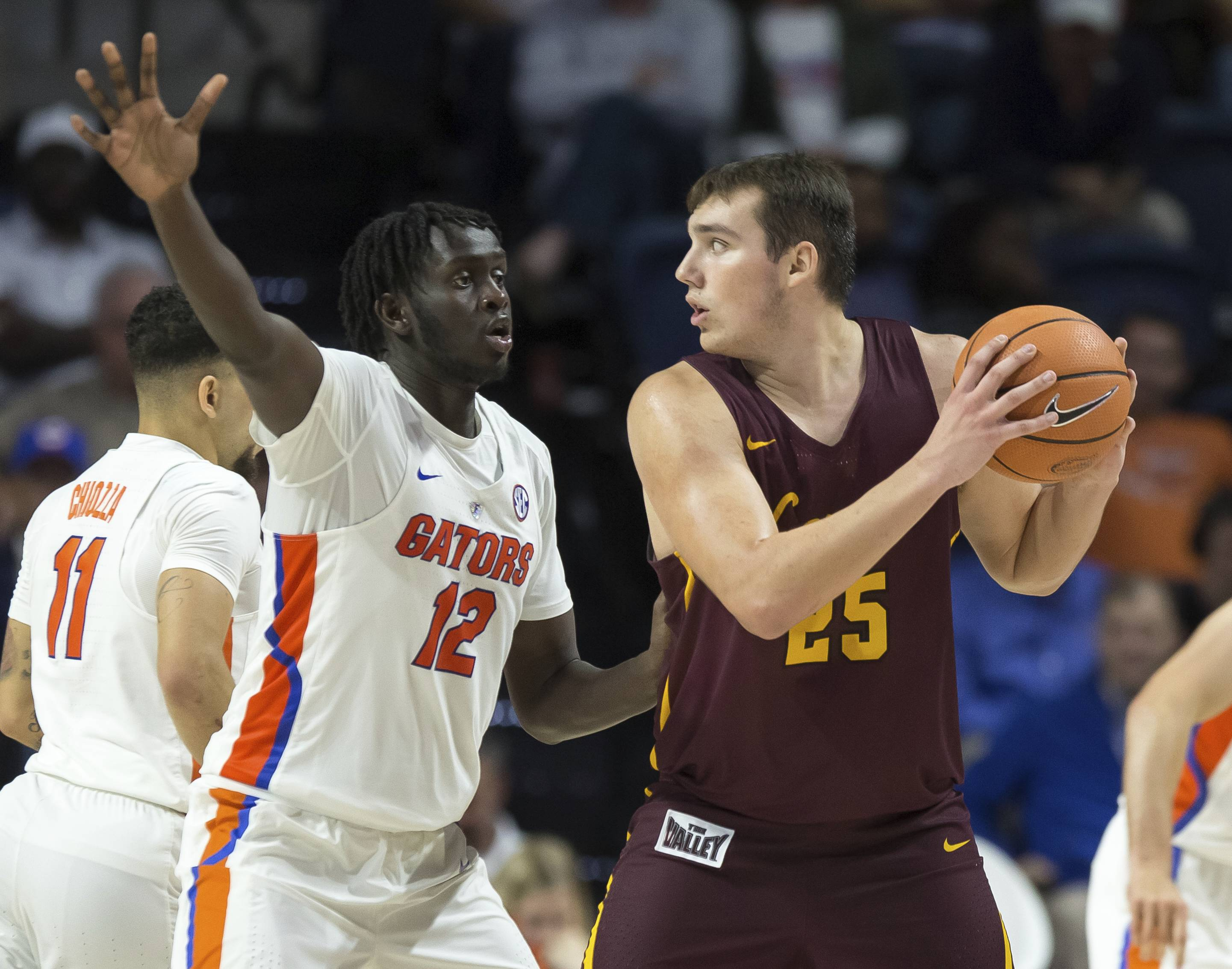 Loyola of Chicago center Cameron Krutwig (25) looks to pass around Florida center Gorjok Gak (12) during the second half of an NCAA college basketball game in Gainesville, Fla., Wednesday, Dec. 6, 2017. Loyola of Chicago won 65-59. (AP Photo/Ron Irby)