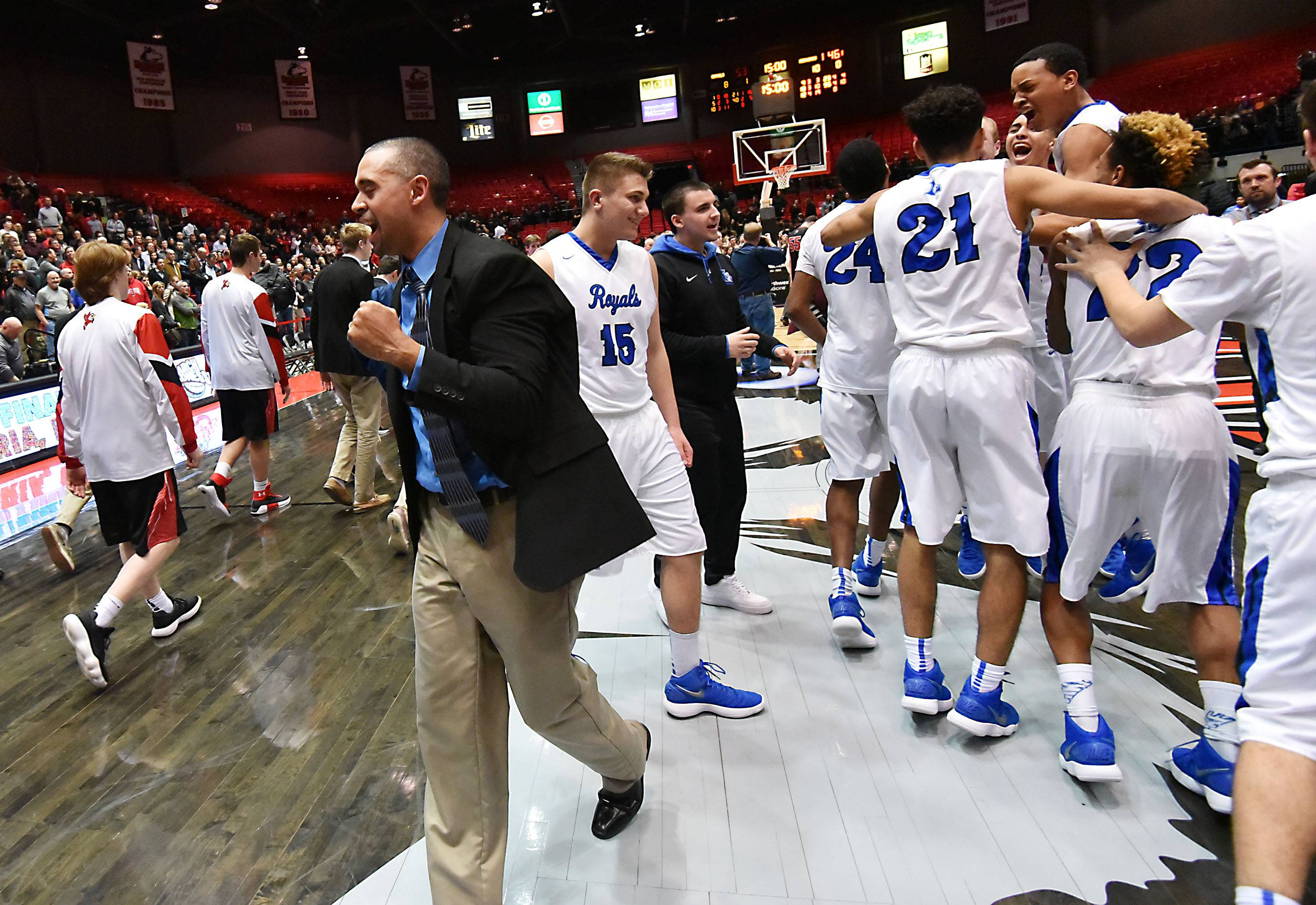 Larkin head coach Deryn Carter pumps his fist as the Royals celebrate their win against Benet in the Class 4A supersectional boys basketball game at Northern Illinois University Tuesday. Larkin takes on Belleville West in the state semifinals Friday in Peoria.