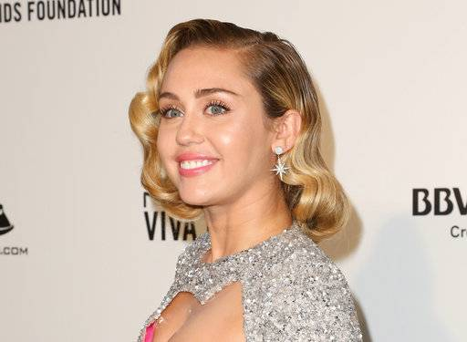 "FILE - In this March 4, 2018 file photo, Miley Cyrus arrives at the 2018 Elton John AIDS Foundation Oscar Viewing Party in West Hollywood, Calif. Jamaican artist Flourgon has filed a lawsuit against Cyrus and Sony Music for the singer's song, ""We Can't Stop.� The lawsuit, filed Tuesday, March 13, 2018, in New York, claims her song borrows from Flourgon's 1988 song, ""We Run Things.� (Photo by Willy Sanjuan/Invision/AP, File)"