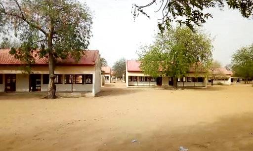 This image taken from video shows the exterior of Government Girls Science and Tech College in Dapchi, Yobe State, Nigeria on Thursday Feb. 22, 2018. As a painful debate about school safety rages in the U.S., President Donald Trump's proposal to put more guns in schools carries echoes of the questions being asked in the northeast Nigeria. Determined to do something, the government has deployed armed guards to schools as parents debate the merits of giving guns to teachers themselves. (AP Photo)