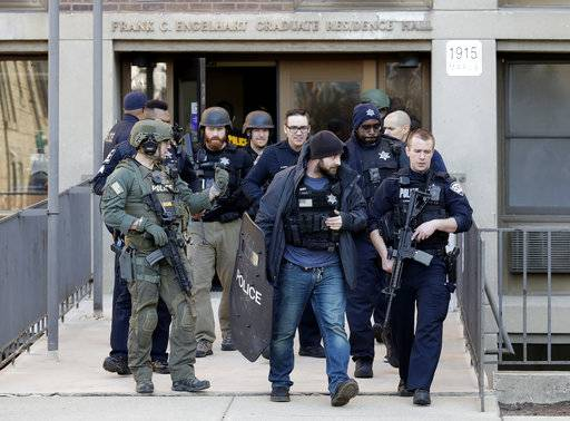 "Evanston police officers leave after an investigation at Northwestern University Engelhart graduate residence hall in Evanston, Ill., Wednesday, March 14, 2018. Police said the report of a gunman at Northwestern University was a hoax and ""swatting incident."" Police said they found no evidence after reports of shots fired on the campus. (AP Photo/Nam Y. Huh)"