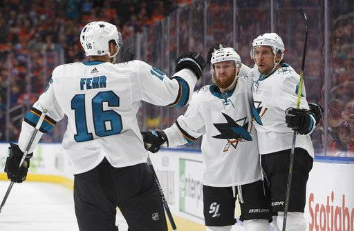San Jose Sharks' Eric Fehr (16), Joakim Ryan (47) and Brenden Dillon celebrate a goal against the Edmonton Oilers during the third period of an NHL hockey game Wednesday, March 14, 2018, in Edmonton, Alberta. (Jason Franson/The Canadian Press via AP)