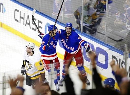 New York Rangers' Mika Zibanejad (93) and Vladislav Namestnikov (90) celebrate after Zibanejad scored a goal to tie the game during the third period of an NHL hockey game as Pittsburgh Penguins Brian Dumoulin (8) reacts Wednesday, March 14, 2018, in New York. The Rangers won 4-3. (AP Photo/Frank Franklin II)