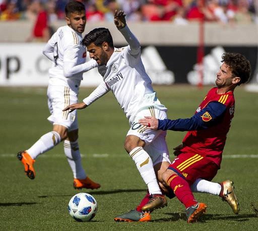 Real Salt Lake midfielder Kyle Beckerman, right, trips up Los Angeles FC forward Carlos Vela (10) during an MLS soccer match at Rio Tinto Stadium in Sandy, Utah, Saturday March 10, 2018. LAFC won 5-1. (Trent Nelson/The Salt Lake Tribune via AP)