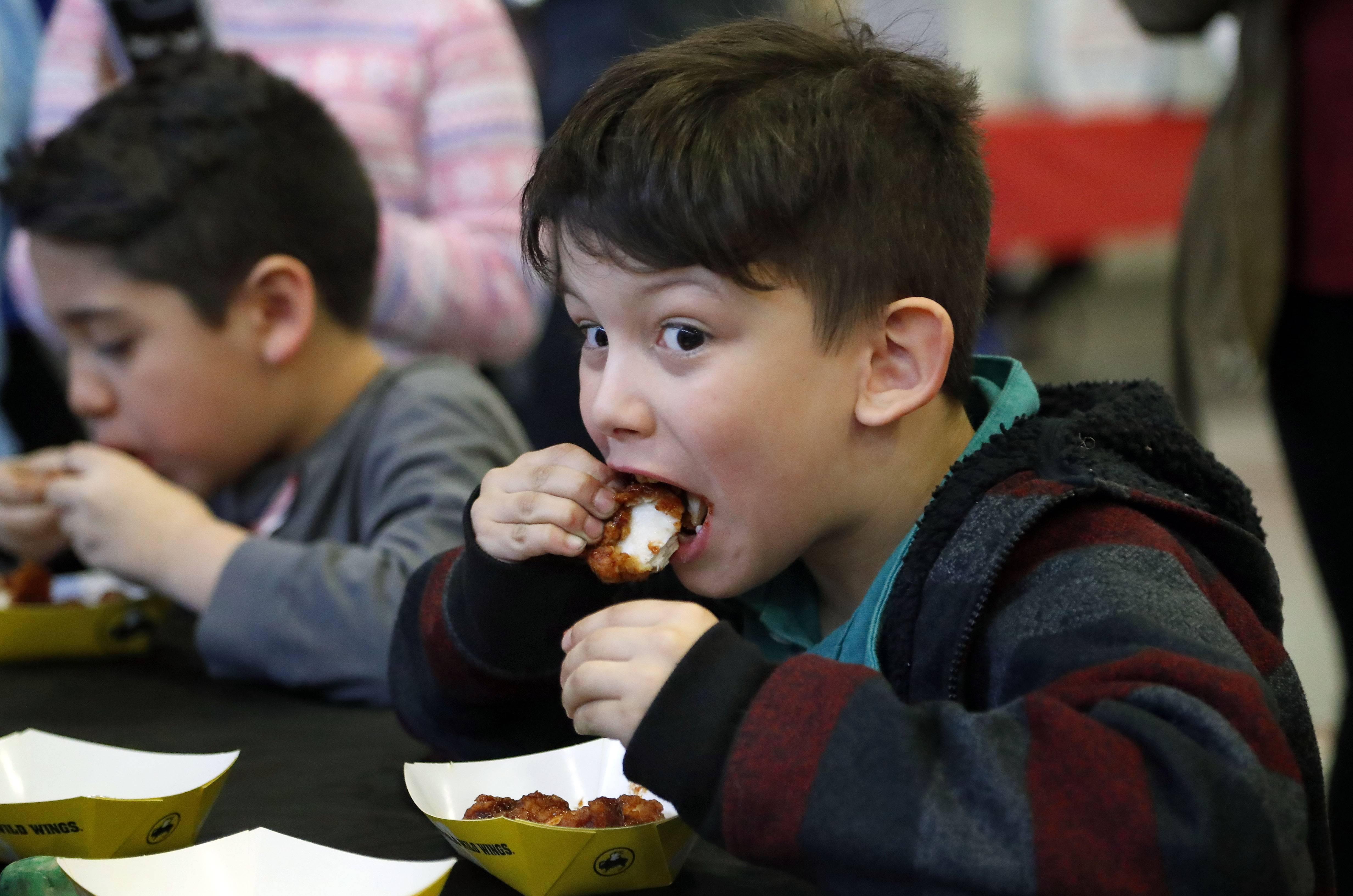 Jaidyn Antosh, 7, of Fox Lake participates in a chicken wing eating contest during the Community Block Party Expo and Craft Fair at the Round Lake Area Park District Sports Center Saturday.