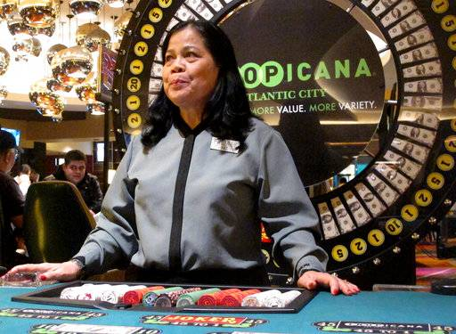 In this March 9, 2016, photo Hat Nguyen, a dealer at the Tropicana casino in Atlantic City N.J., waits for customers at the cash wheel game. On Monday April 16, 2018, Carl Icahn sold the real estate assets of Tropicana Entertainment to Gaming and Leisure Properties, and its casino operations to Eldorado Resorts in a $1.85 billion deal. Tropicana's casino in Aruba is not part of the deal.