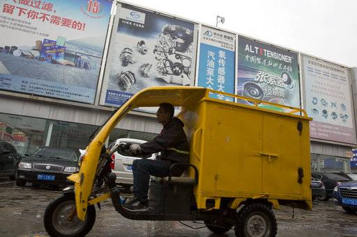 In this April 13, 2018 photo, a delivery past by a auto parts market in Beijing, China. Chinese exporters of goods from electronics to motorcycle parts are scrambling to insulate themselves from U.S. President Donald Trump's proposed tariff hike. They are weighing plans to rush shipments to American customers ahead of the increase, raise prices or find other markets. Some are looking at shipping goods through other countries to hide their Chinese origin.