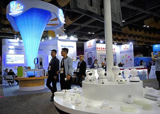 In this April 11, 2018 photo, people walk past electronics products at the Global Sources trade fair, a trade fair where Chinese manufacturers meet western buyers in Hong Kong. Chinese exporters of goods from electronics to motorcycle parts are scrambling to insulate themselves from U.S. President Donald Trump's proposed tariff hike.