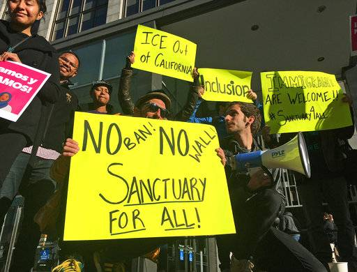 FILE - In this April 14, 2017, file photo, protesters rally outside a courthouse where a federal judge heard arguments in the first lawsuit challenging President Donald Trump's executive order to withhold funding from communities that limit cooperation with immigration authorities in San Francisco. U.S. District Judge William Orrick on Monday, March 5, 2018, rejected the state's request for a preliminary injunction to turn over the money. More local governments in California are resisting the state's efforts to resist the Trump administration's immigration crackdown, and political experts see politics at play as Republicans try to fire up voters in a state where the GOP has grown weak.