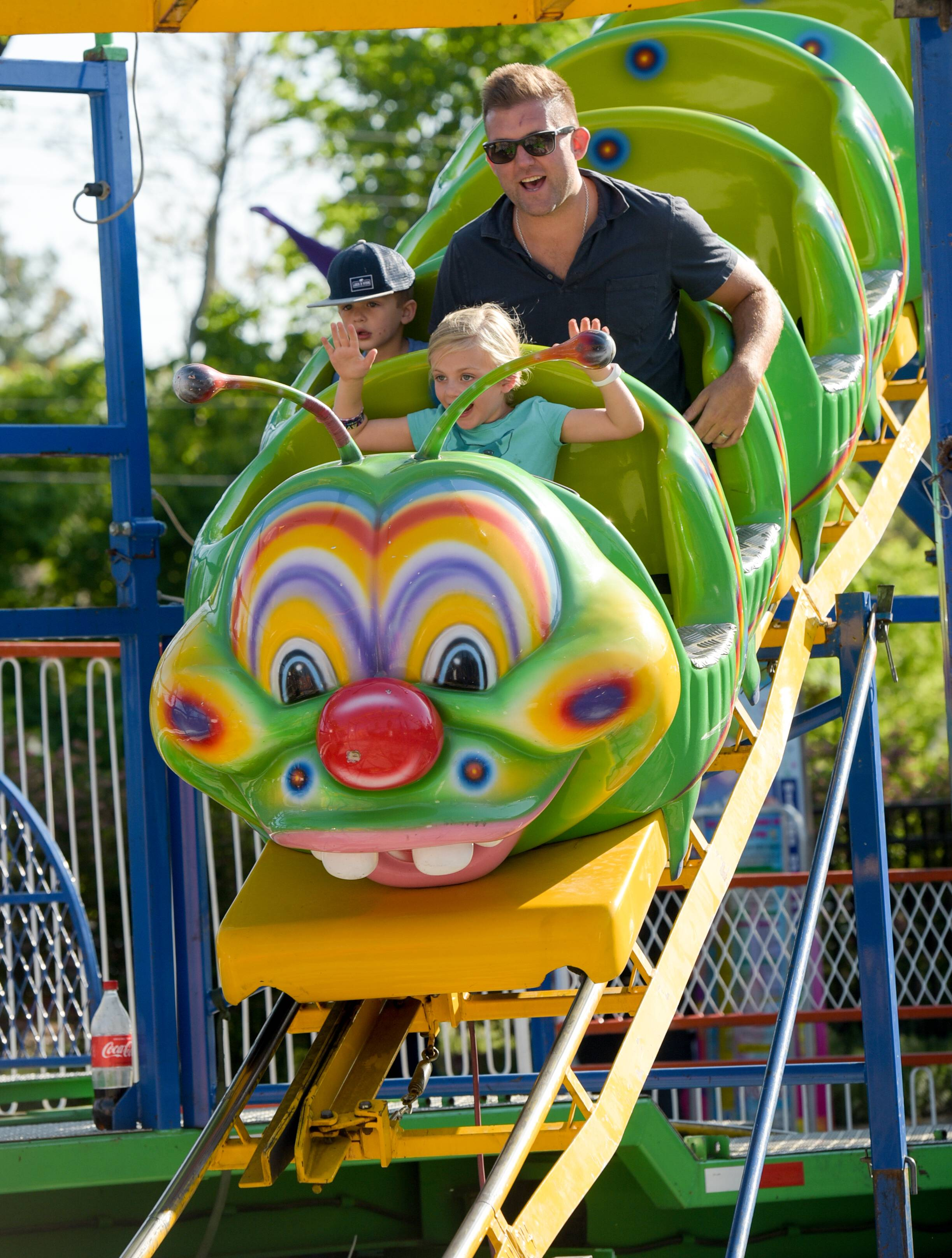 Glen Ellyn dad Tom Kolesti takes a ride on a caterpillar roller coaster Wednesday with his kids Tommy, 3, and Keira, 6, on the opening day of a carnival that runs in conjunction with the Taste of Glen Ellyn, a long-running festival returning Thursday.