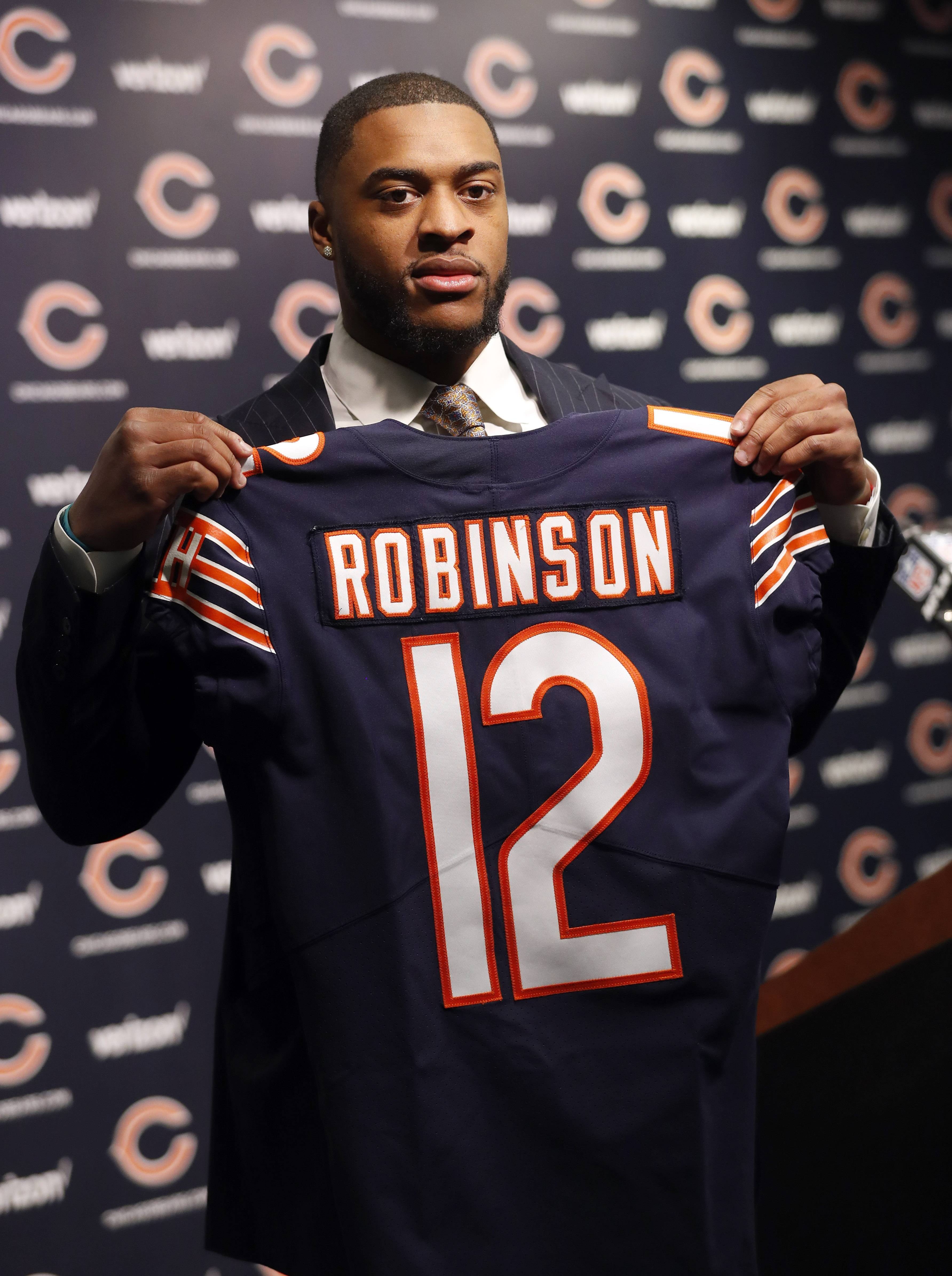 Steve Lundy/slundy@dailyherald.comWide receiver free agent signee Allen Robinson holds up his jersey during a press conference at Halas Hall in Lake Forest Thursday.