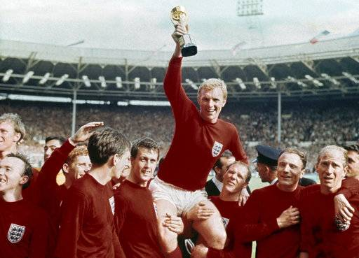 FILE - In this July 30, 1966 file photo, England's soccer captain Bobby Moore, center, is carried by teammates Geoff Hurst, center left, and Ray Wilson as he holds FIFA World Cup after England defeated Germany 4-2 in the final at London's Wembley Stadium. Ray Wilson, the left back for all six of England's games in its World Cup-winning campaign in 1966, has died. He was 83. Former club Huddersfield announced Wilson's death on Wednesday, May 16, 2018.