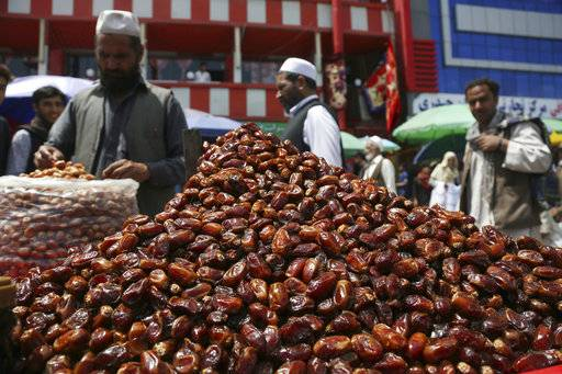 A street vendor sells dates ahead of the upcoming holy fasting month of Ramadan in Kabul, Afghanistan, Wednesday, May 16, 2018. Muslims across the world are observing the holy fasting month of Ramadan, when they refrain from eating, drinking and smoking from dawn to dusk.