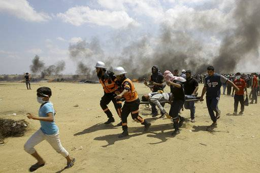 FILE - In this Monday, May 14, 2018 file photo, Palestinian medics and protesters evacuate a wounded youth during a protest at the Gaza Strip's border with Israel, east of Khan Younis, Gaza Strip. Arab states resoundingly condemned the killing of more than 50 Palestinians on Monday, May 14, 2018 in Gaza protests, just as they have after previous Israeli violence going back decades. But behind the scenes, fears over Iran have divided Arab leaders, with some willing to quietly reach out to Israel.
