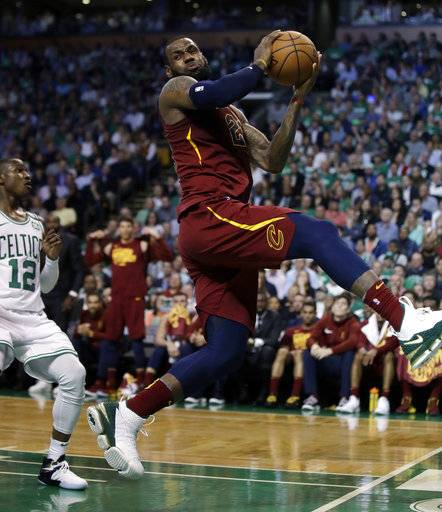 Cleveland Cavaliers forward LeBron James recoils after colliding with Boston Celtics forward Jayson Tatum, out of picture, in front of Celtics guard Terry Rozier, left, during the first half in Game 2 of the NBA basketball Eastern Conference finals, Tuesday, May 15, 2018, in Boston.