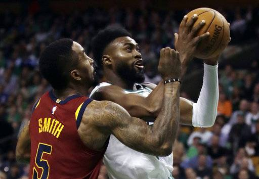 Boston Celtics guard Jaylen Brown, right, tries to drive against Cleveland Cavaliers guard JR Smith (5) during the second half in Game 2 of the NBA basketball Eastern Conference final, Tuesday, May 15, 2018, in Boston.