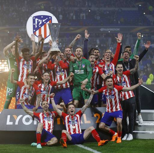 Atletico players with head coach Diego Simeone, far right in black, celebrate with the trophy after winning the Europa League Final soccer match between Marseille and Atletico Madrid at the Stade de Lyon in Decines, outside Lyon, France, Wednesday, May 16, 2018.