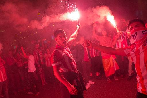Atletico Madrid supporters light flares as they celebrate their team's Europa League tittle in Madrid, Wednesday, May 16, 2018. Atletico defeated Marseille 3-0 in the final and clinches its third Europa League title.