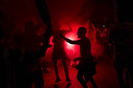 Atletico Madrid supporters light flares as they celebrate their team's Europa League title in Madrid, early Thursday, May 17, 2018. Atletico defeated Marseille 3-0 in the final and clinches its third Europa League title.