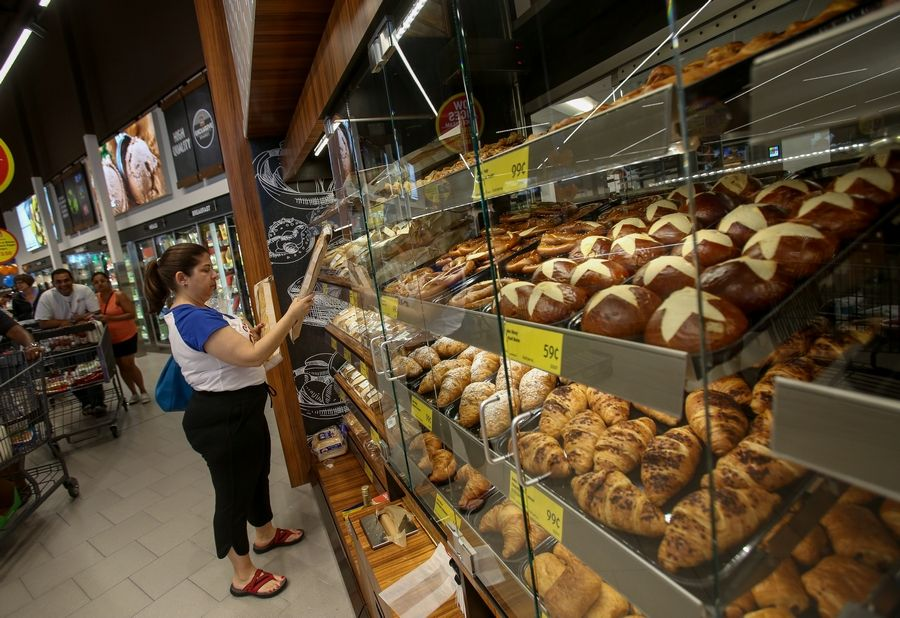 Kim Berger of Naperville selects bread from the bakery section of Naperville's new Aldi store.