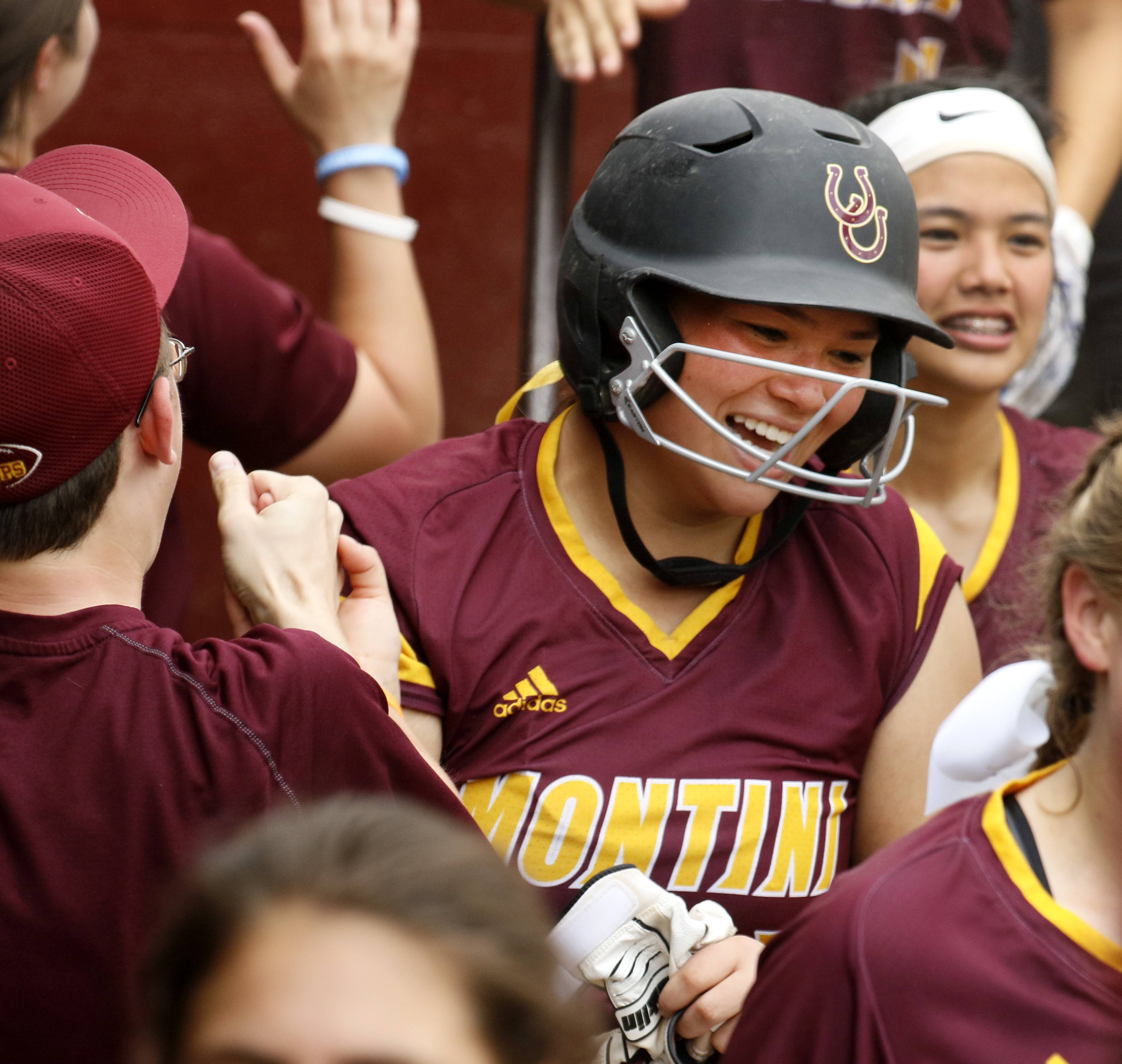 Montini Catholic's Nicole Cuchran is congratulated after hitting a home run against Kaneland during the IHSA Class 3A state softball championship.