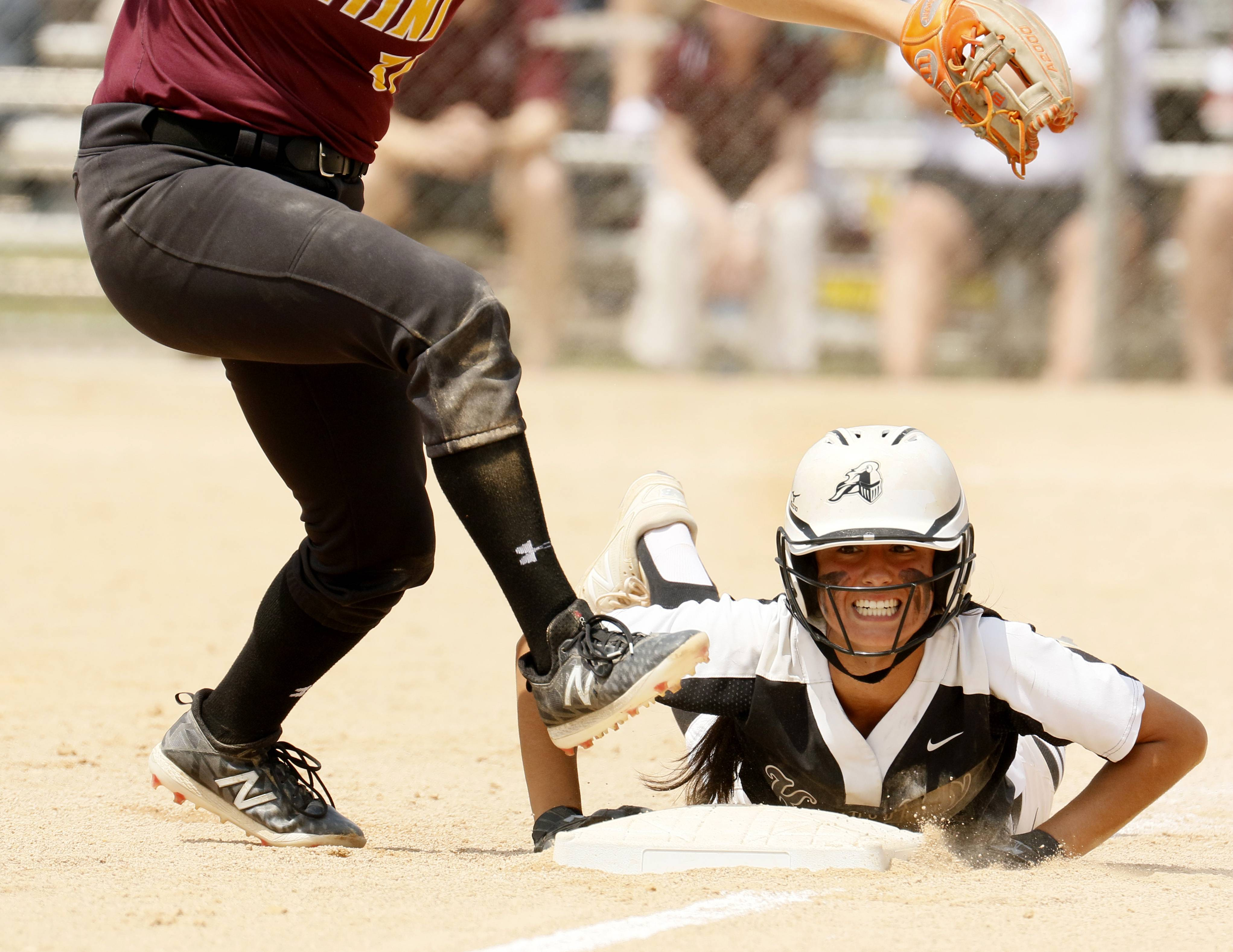Kaneland's Donatela Sommesi slides back into third base and watches an errant throw fly down the left field line against Montini Catholic during the IHSA Class 3A state softball championship.