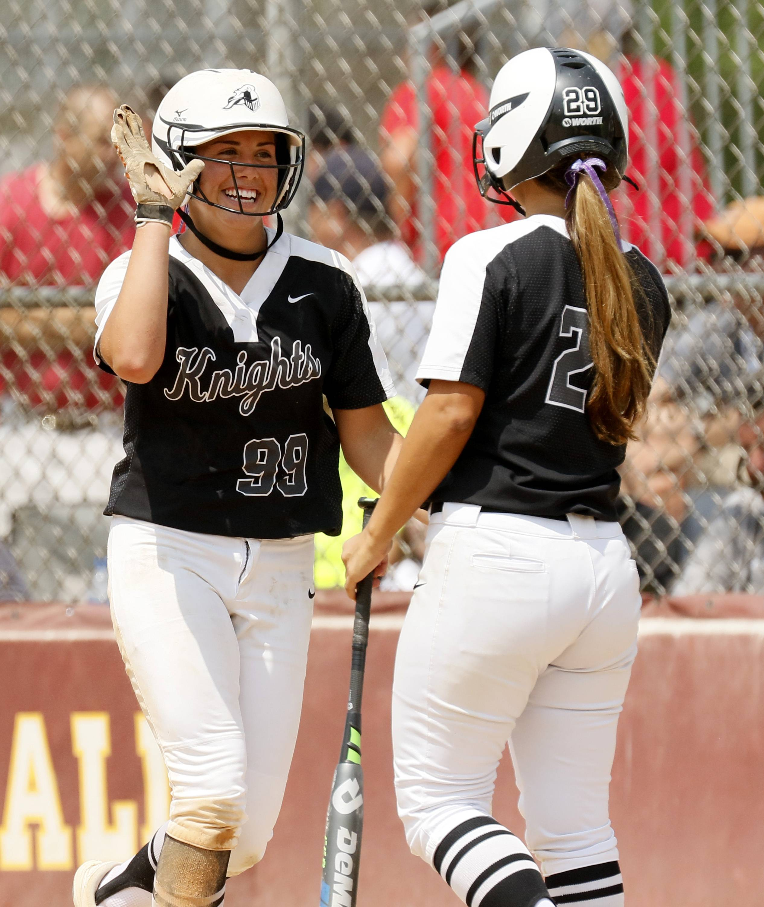 Kaneland's Rose Roach (99) gets a high-five after scoring a run against Montini Catholic during the IHSA Class 3A state softball championship.