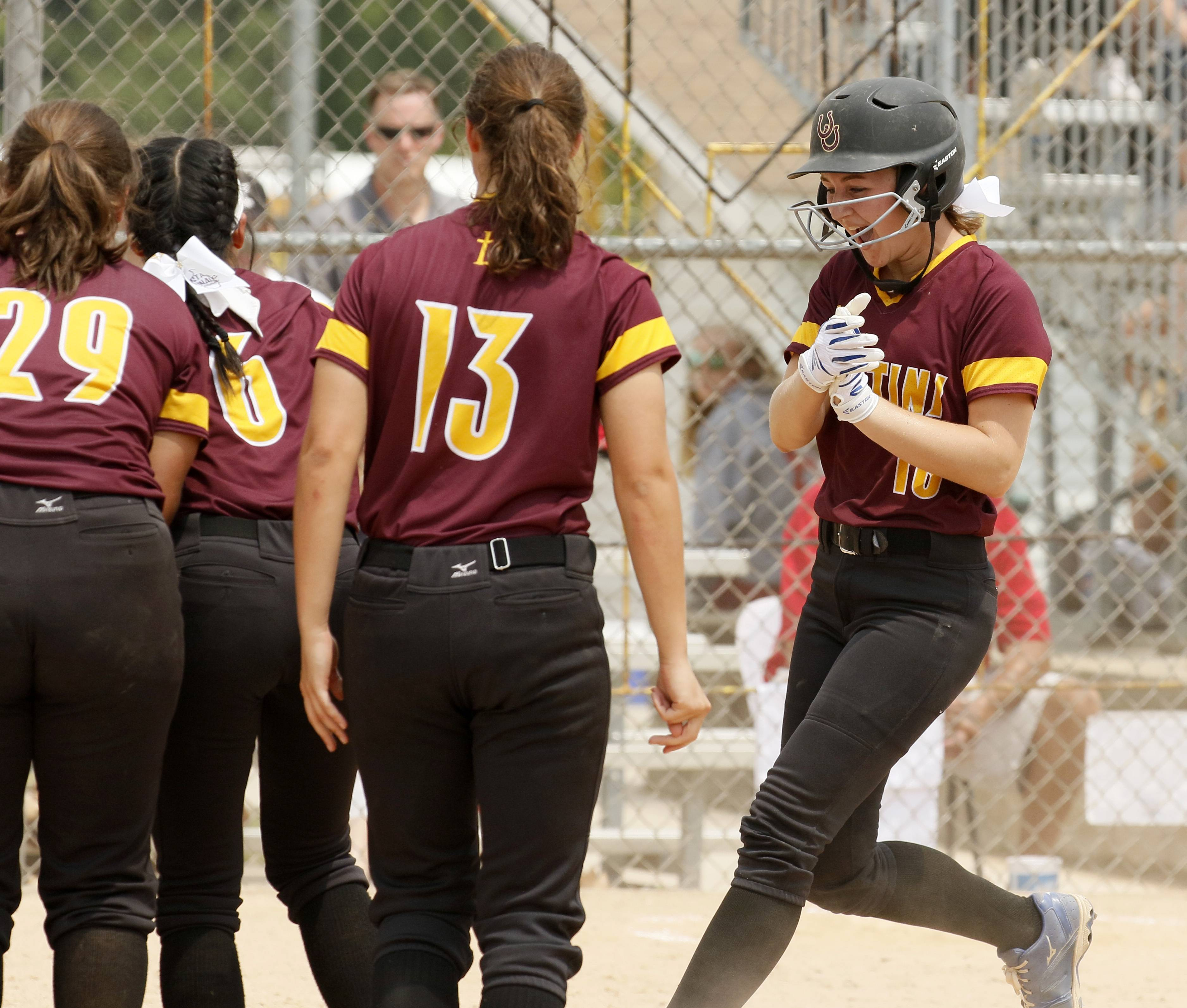 Montini Catholic's Alyssa Filkowski (18) is greeted at home plate after hitting a home run against Kaneland during the IHSA Class 3A state softball championship.