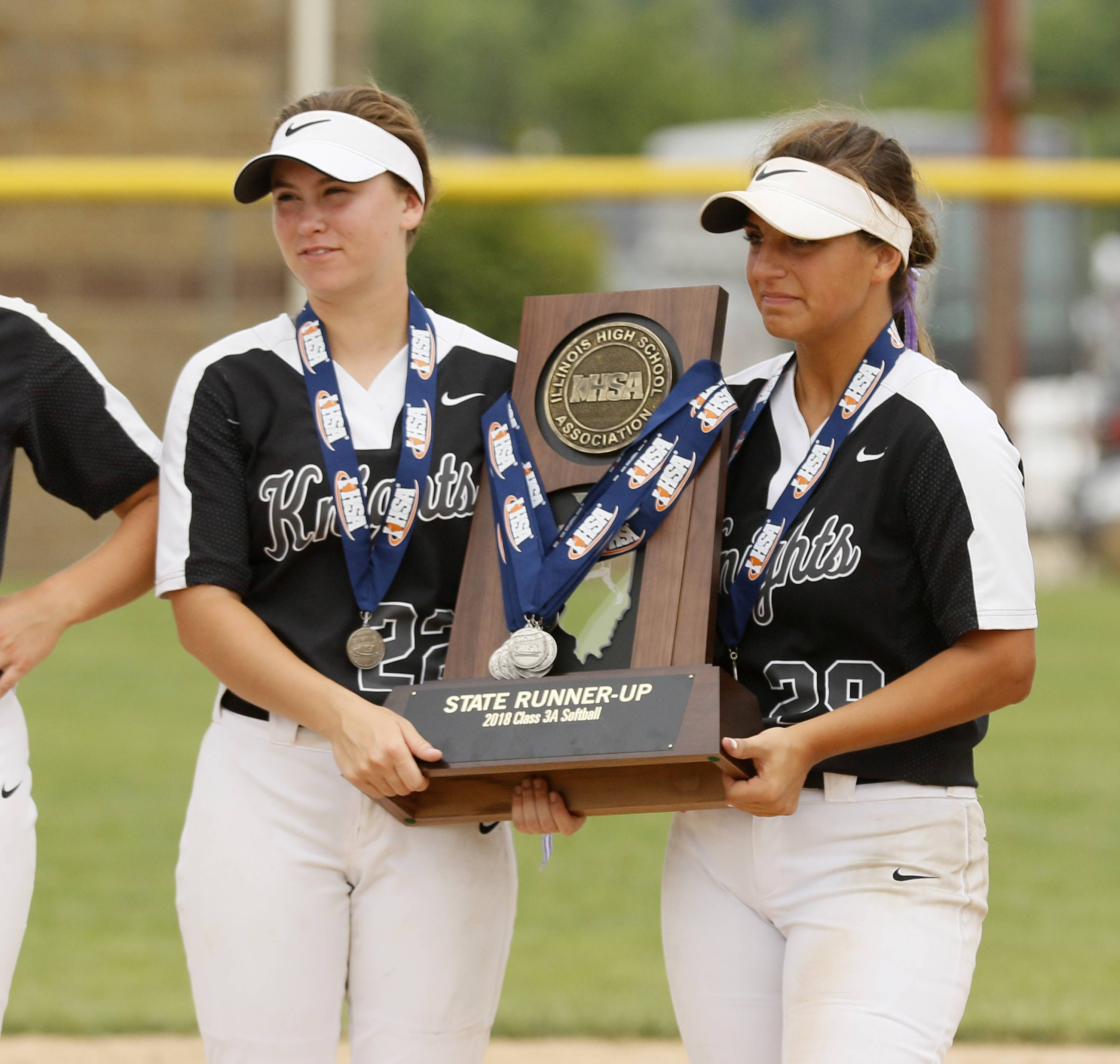 Kaneland players pose with the second place trophy following the IHSA Class 3A state softball championship.
