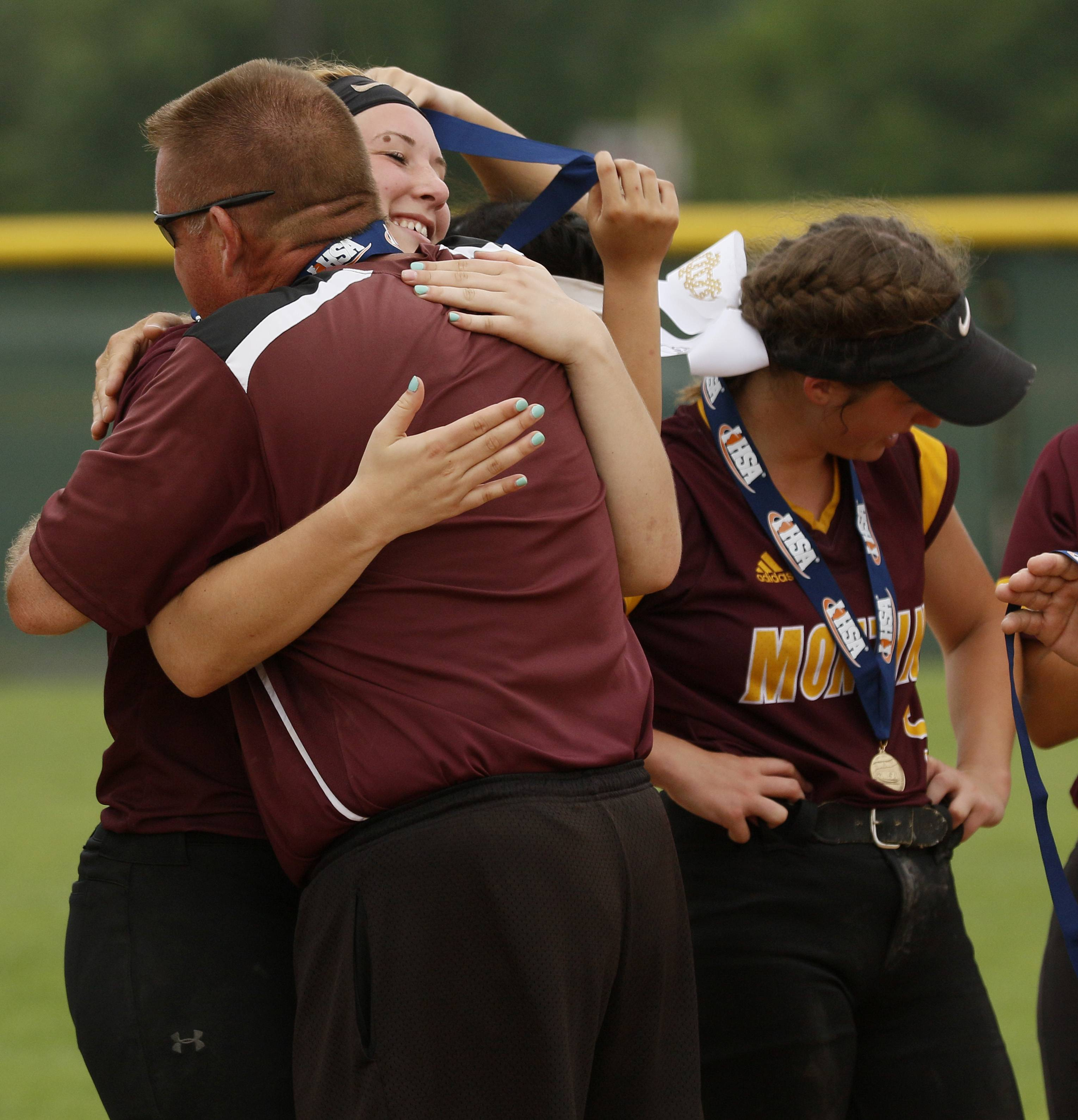Montini Catholic players and coaches celebrate their epic 15-8 seventh inning comeback against Kaneland to win the IHSA Class 3A state softball championship.