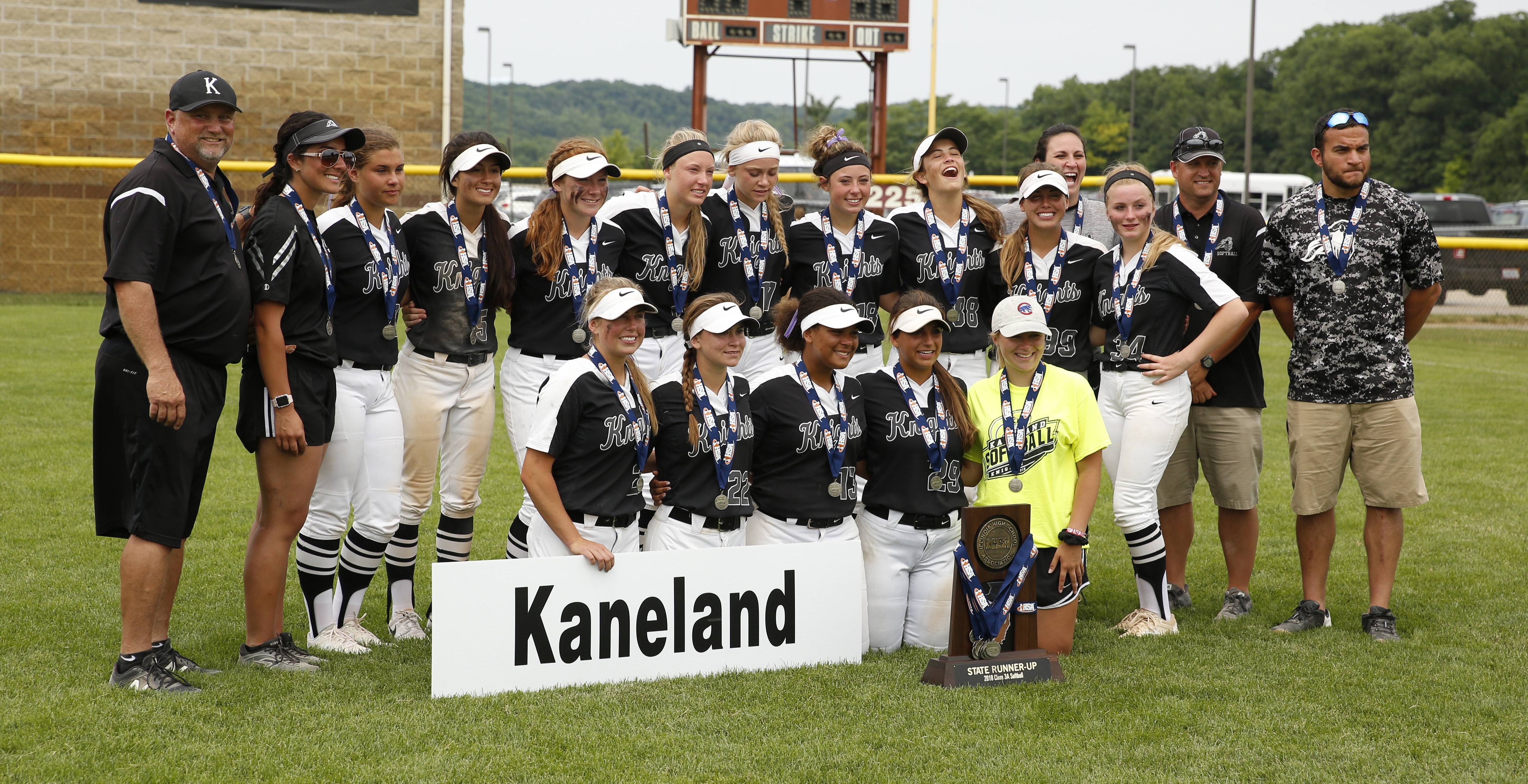 Kaneland players pose with the second place trophy following the IHSA Class 3A state softball championship game.