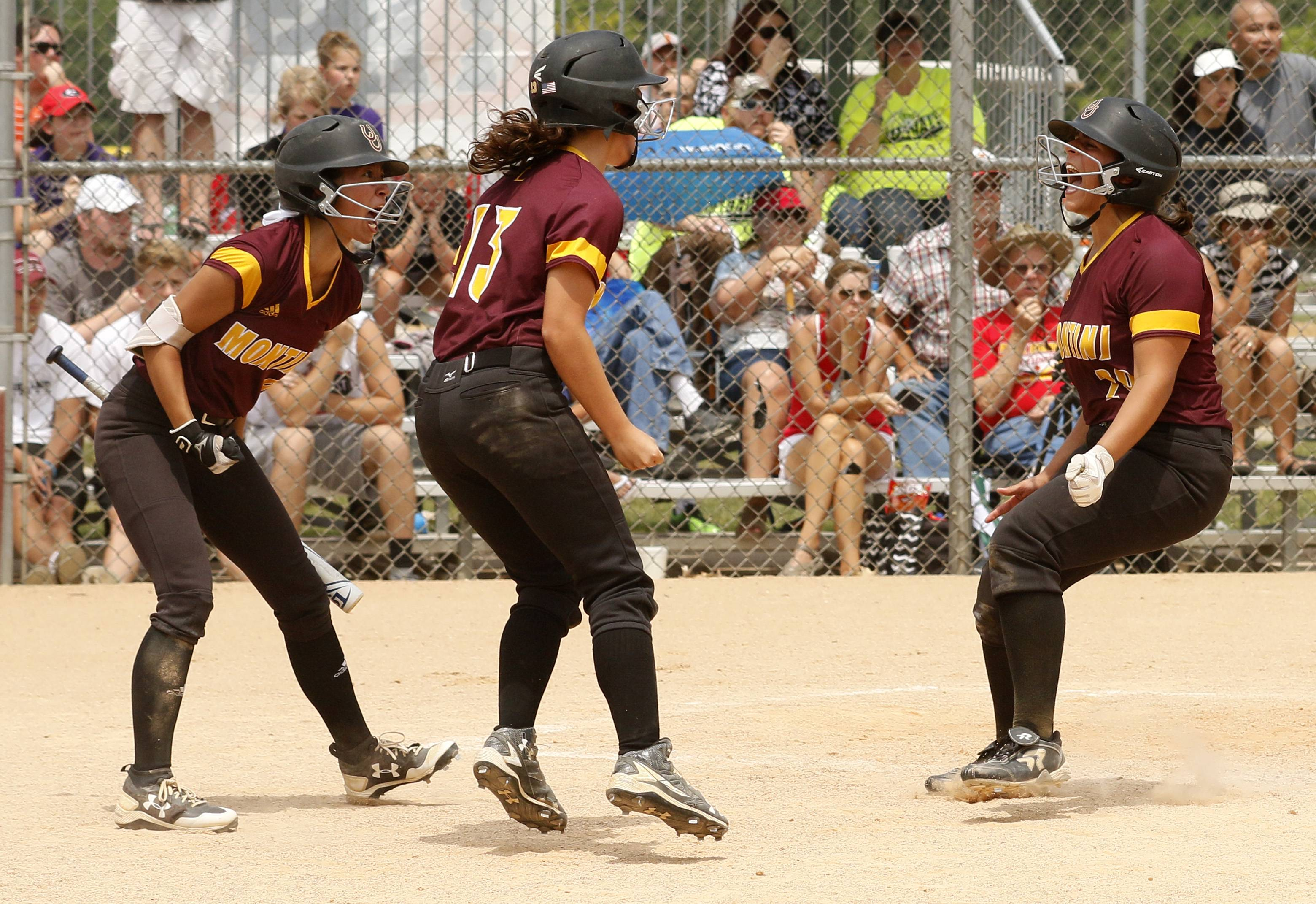 Montini Catholic's Else Spaccapaniccia (29) is greeted at home plate against Kaneland during the IHSA Class 3A state softball championship.