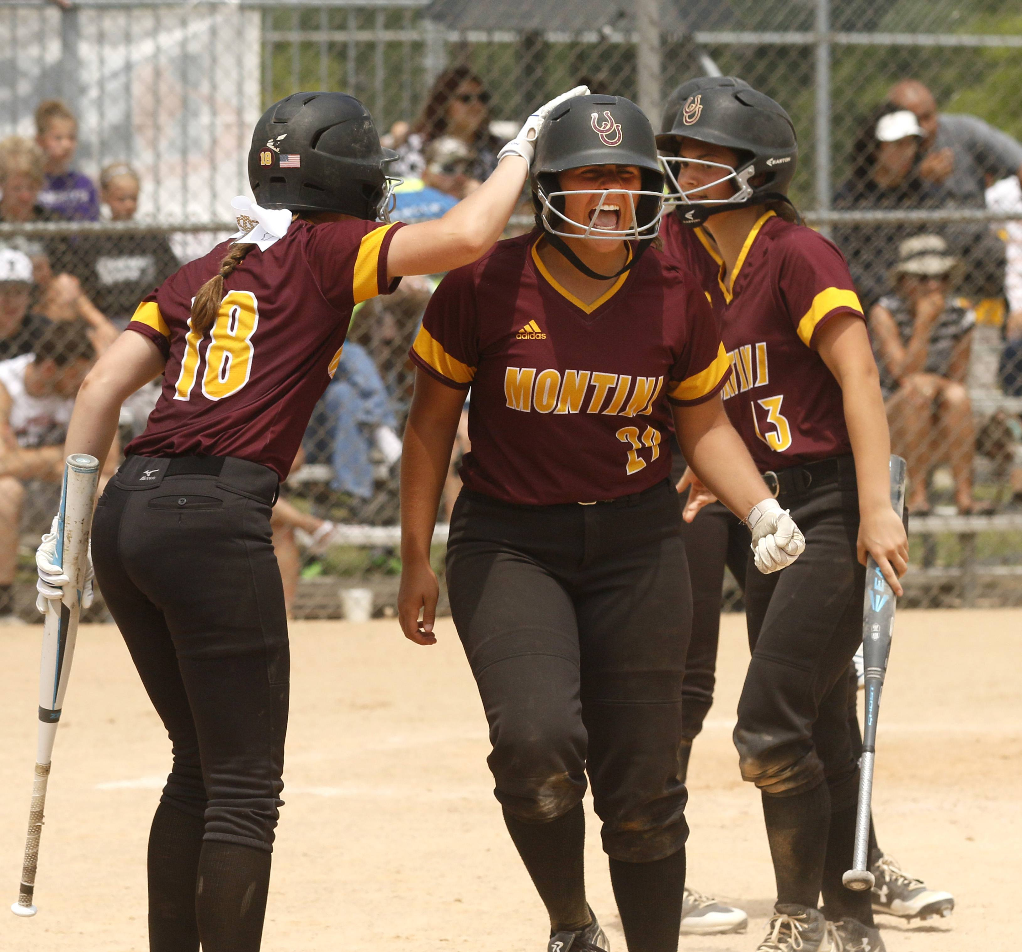 Montini Catholic's Else Spaccapaniccia (29) is greeted at home plate by Alyssa Filkowski (18) against Kaneland during the IHSA Class 3A state softball championship.