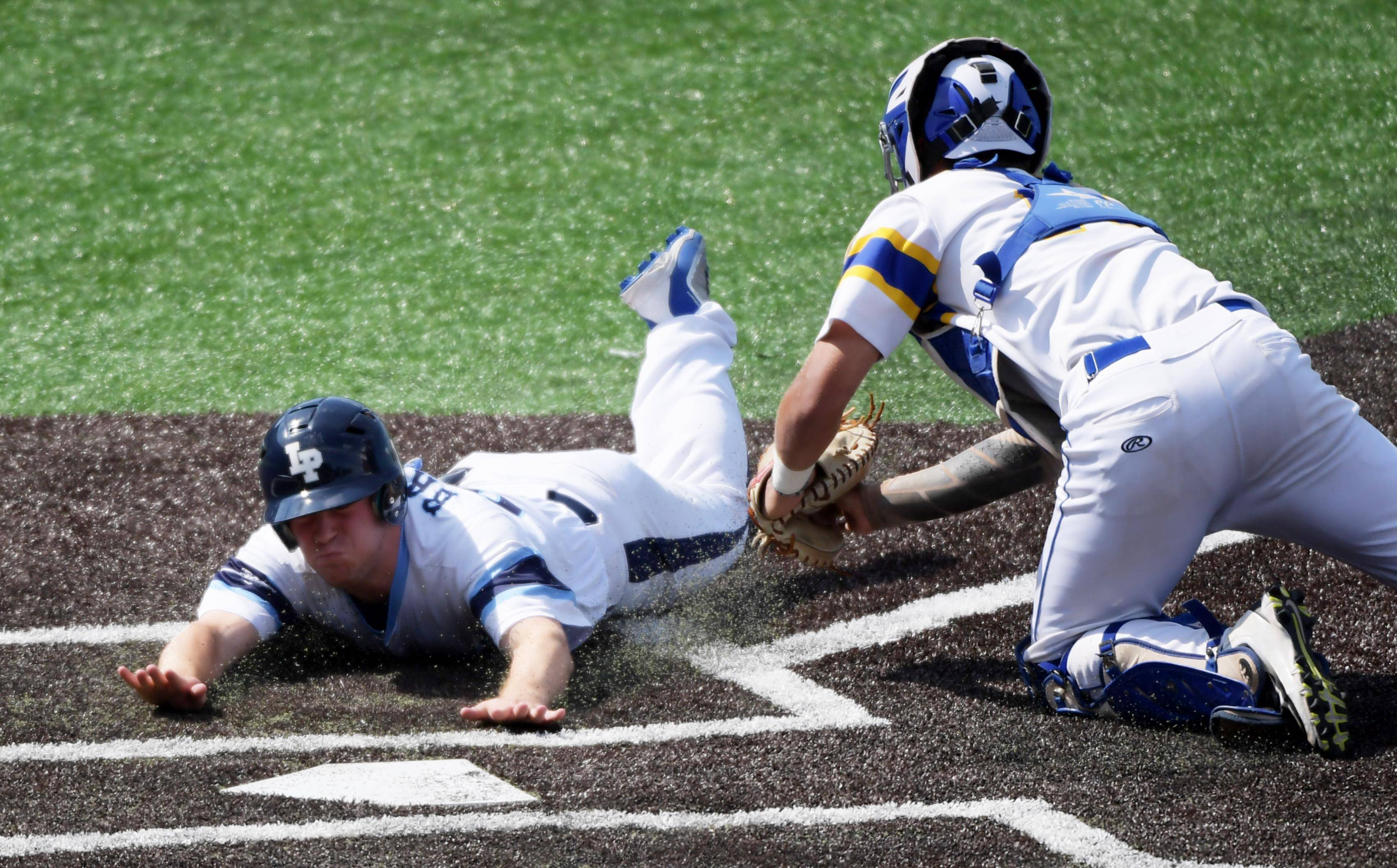 Lake Park's Anthony Baturin slides safely into home as Sandburg catcher Ryan Hampe reaches for him in the Class 4A state baseball third place game at Route 66 Stadium in Joliet Saturday.