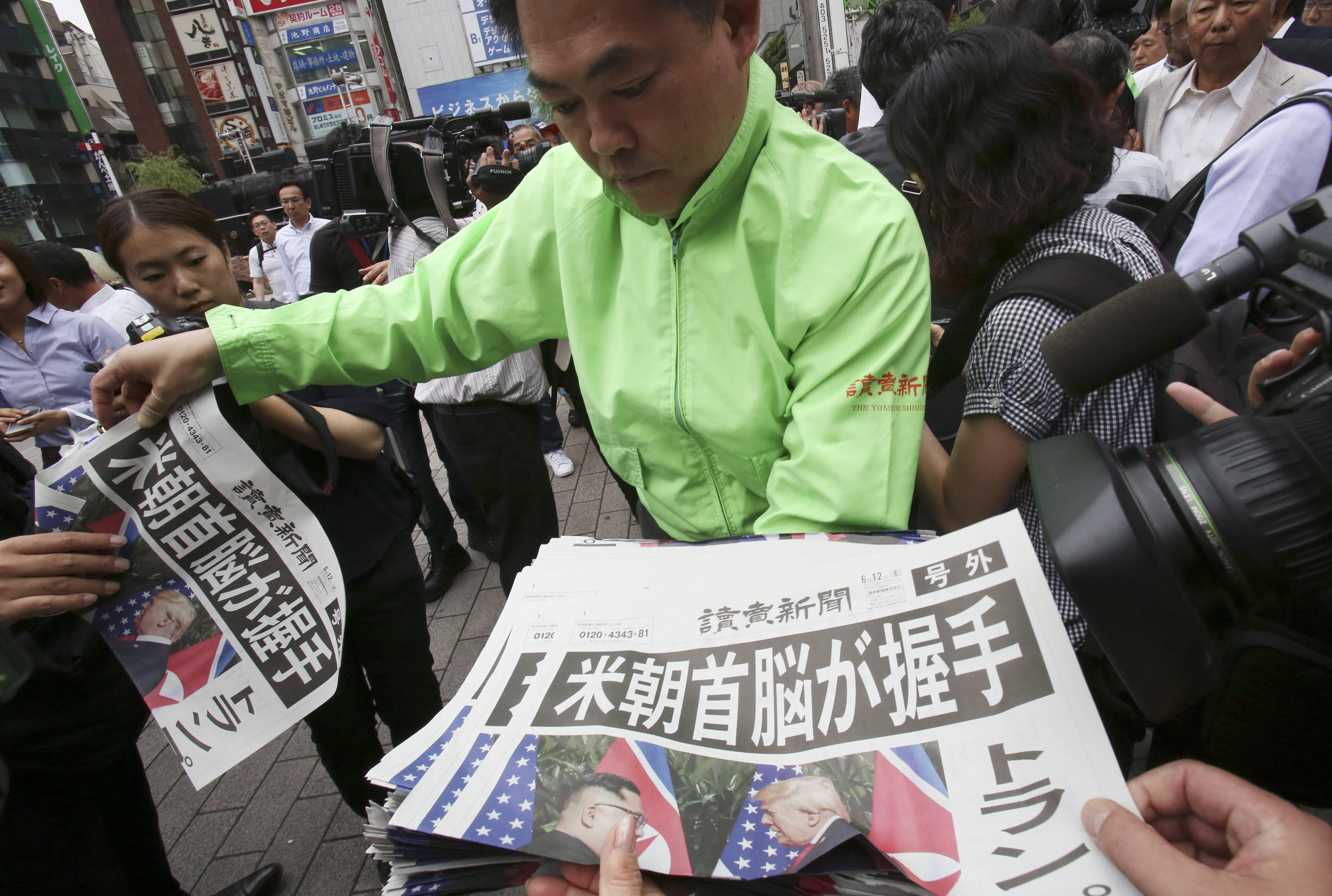 A staff of a Japanese news paper Yomiuri distributes an extra edition of the newspaper reporting about the summit between U.S. President Donald Trump and North Korean leader Kim Jong Un in Singapore, at Shimbashi Station in Tokyo, Tuesday.