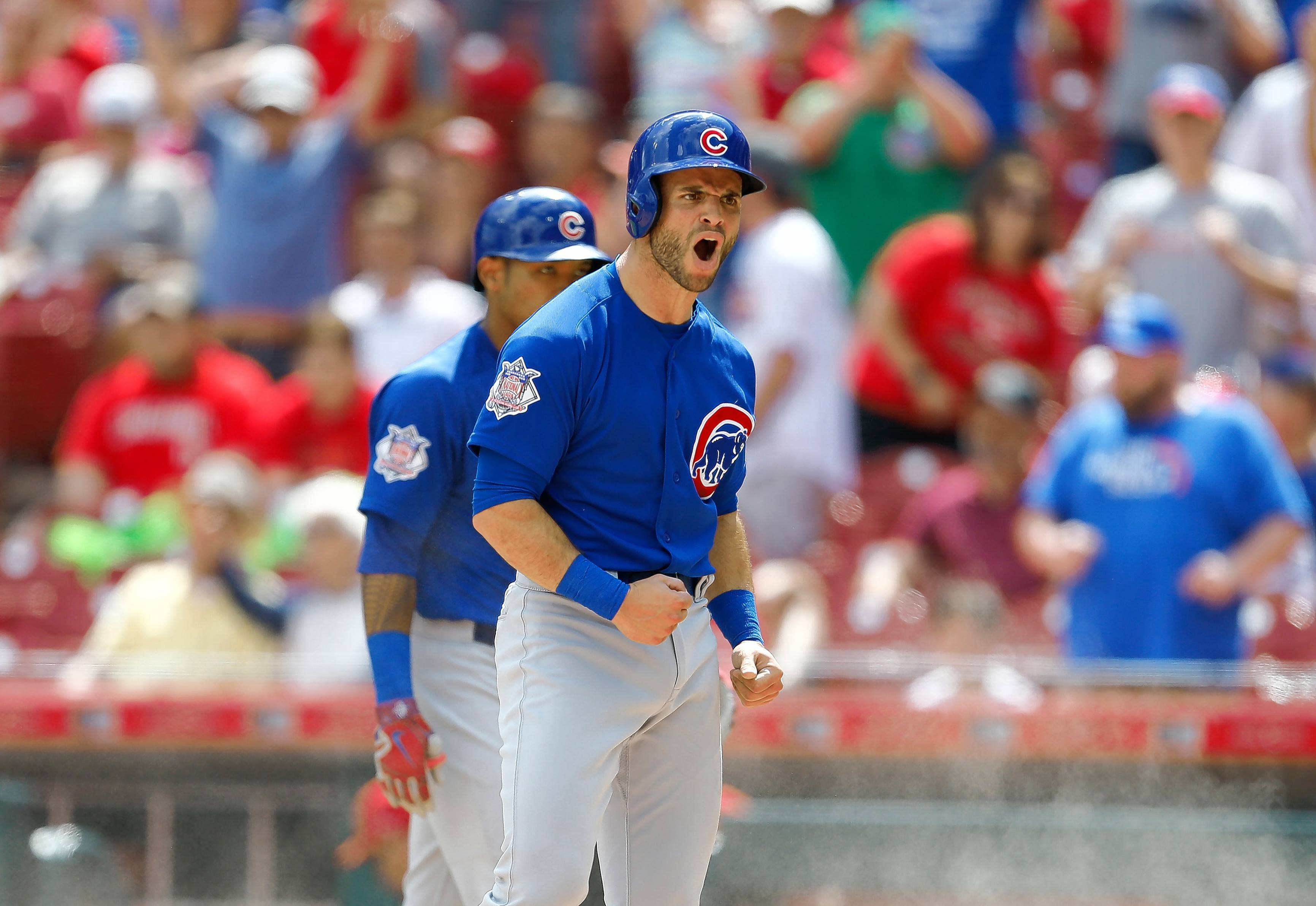 Chicago Cubs' Tommy La Stella, front, reacts to scoring on a double by Anthony Rizzo during the eighth inning in the first baseball game of a doubleheader against the Cincinnati Reds, Saturday, May 19, 2018, in Cincinnati. The Reds won 5-4 in 11 innings.