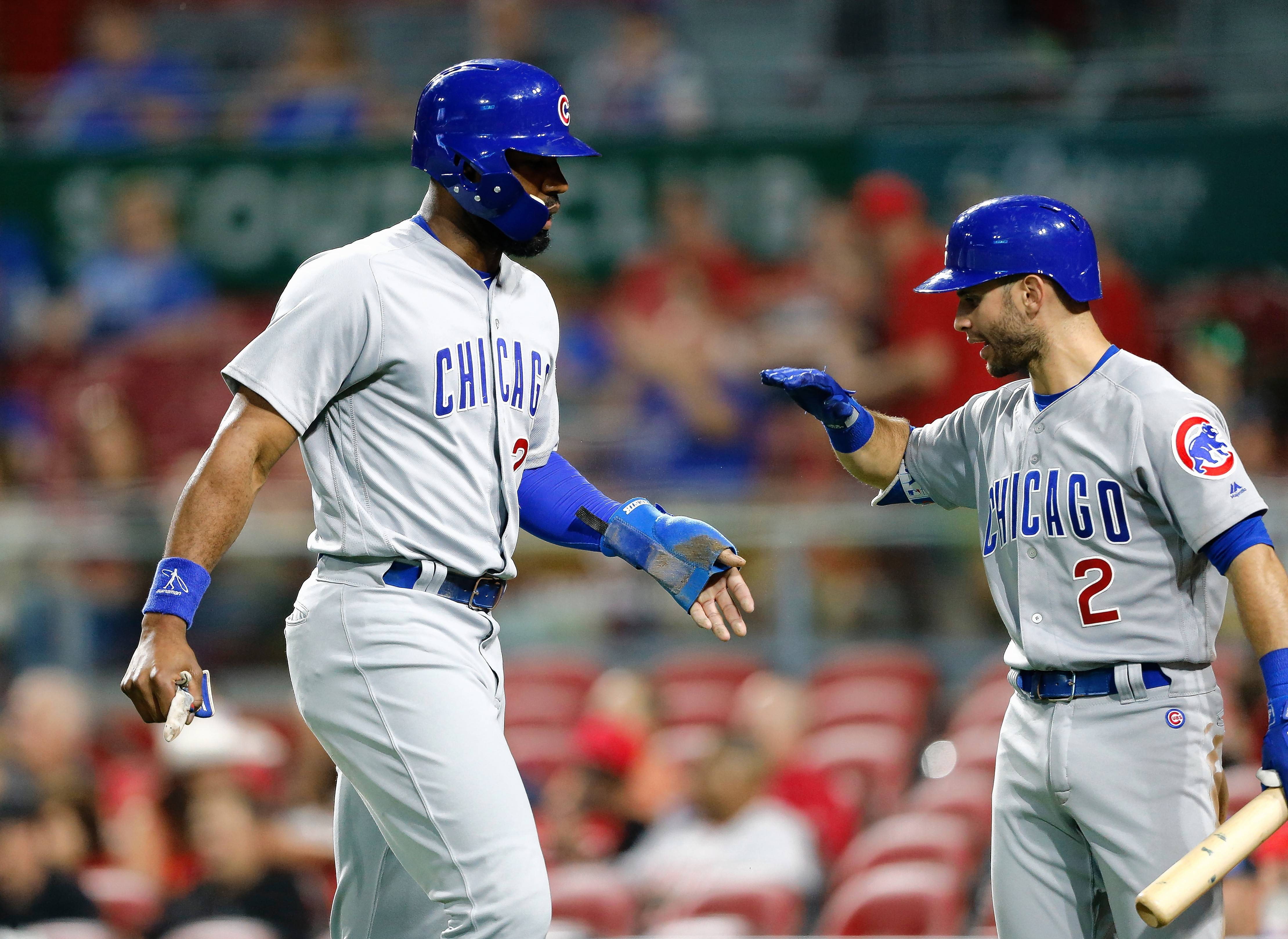 Chicago Cubs' Jason Heyward, left, is congratulated by Tommy La Stella (2) after scoring on a double by Albert Almora Jr. against the Cincinnati Reds during the ninth inning in the second baseball game of a doubleheader, Saturday, May 19, 2018, in Cincinnati. The Cubs won 10-0.