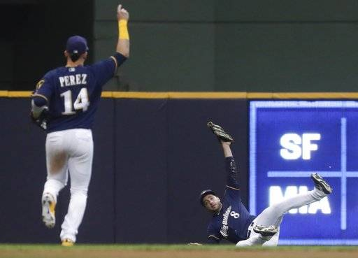 Milwaukee Brewers' Ryan Braun makes a diving catch on a ball hit by Chicago Cubs' Anthony Rizzo during the fourth inning of a baseball game Monday, June 11, 2018, in Milwaukee.