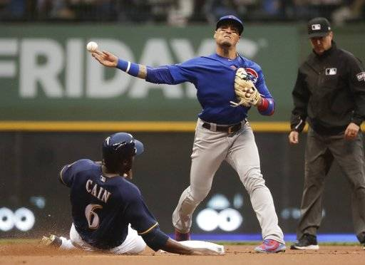 Milwaukee Brewers' Lorenzo Cain is out at second as Chicago Cubs' Javier Baez turns a double play on a ball hit by Christian Yelich during the first inning of a baseball game Monday, June 11, 2018, in Milwaukee.