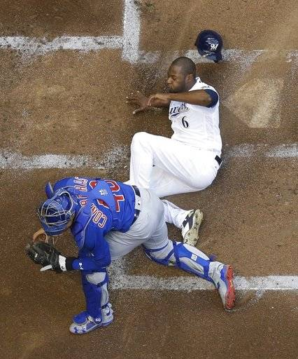 CORRECTS TO DOUBLE, INSTEAD OF TRIPLE - Milwaukee Brewers' Lorenzo Cain slides safely past Chicago Cubs catcher Willson Contreras during the first inning of a baseball game Tuesday, June 12, 2018, in Milwaukee. Cain scored on a two-run double by Travis Shaw.