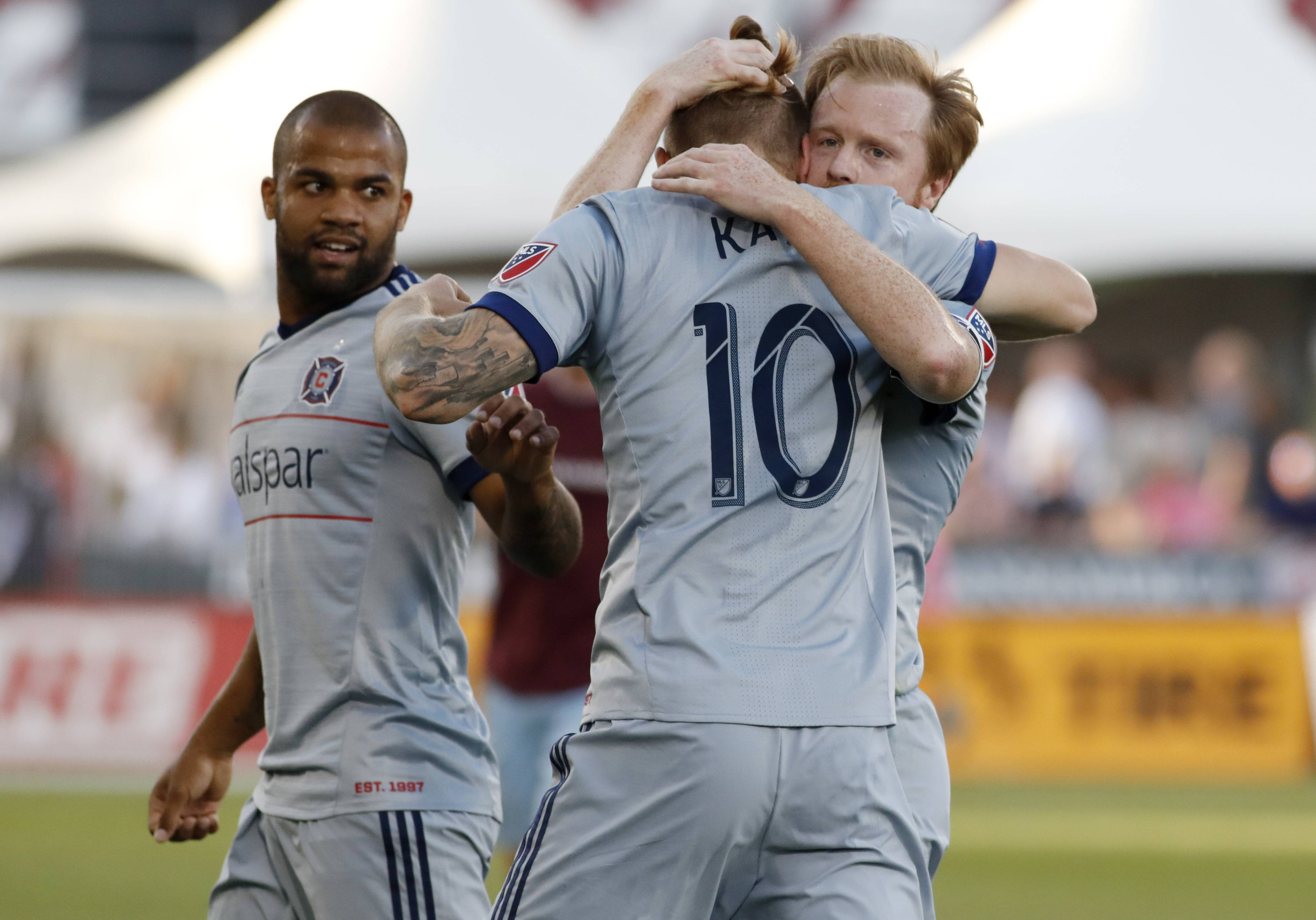 Chicago Fire forward Aleksandar Katai, center, is hugged by midfielder Dax McCarty, right, as defender Kevin Ellis looks over at them after Katai's goal against Colorado Rapids goalkeeper Tim Howard during the first half of an MLS soccer match Wednesday, June 13, 2018, in Commerce City, Colo.