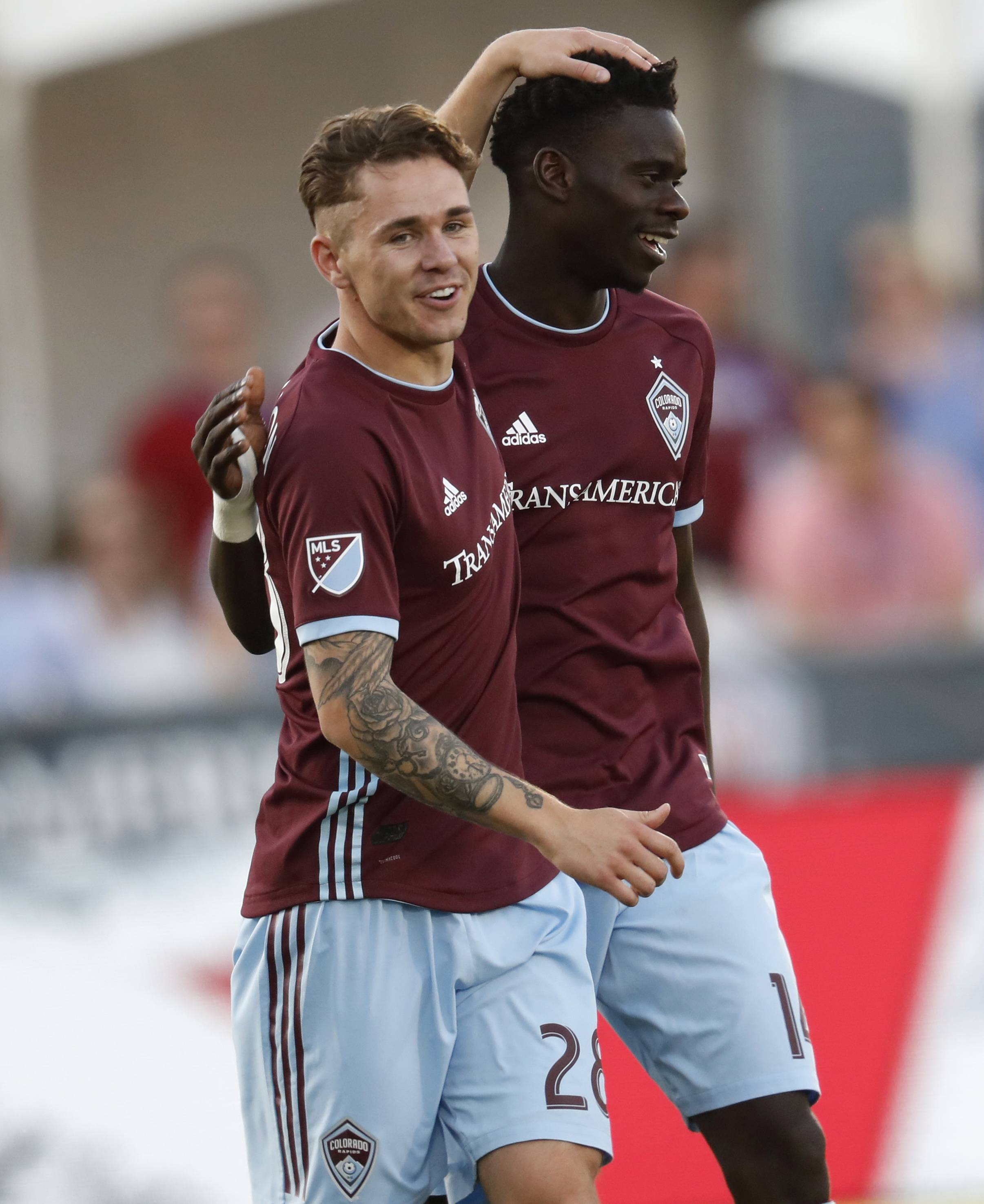 Colorado Rapids midfielder Sam Nicholson, front, congratulates forward Dominique Badji for his goal against the Chicago Fire during the first half of an MLS soccer match Wednesday, June 13, 2018, in Commerce City, Colo.