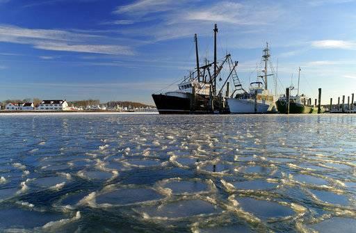 Surrounded by ice, commercial fishing boats are docked in their slips after more than a week's worth of frigid weather froze the harbor in Lake Montauk in Montauk, N.Y., on Sunday, Jan. 7, 2018. Only a few commercial boats remain in Montauk harbor during the winter months fishing for species such as porgy, tilefish, monkfish and black sea bass.