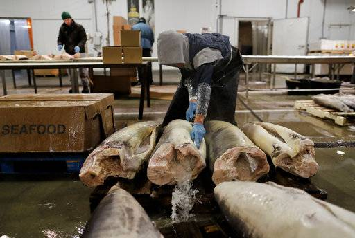 A fishmonger rinses swordfish carcasses just pulled from their shipping containers at the New Fulton Fish Market in New York on Monday, Jan. 8, 2018. The U.S. seafood industry is worth $17 billion a year, more than 90 percent of which is made up of imports. Experts say one in five fish is caught illegally worldwide.