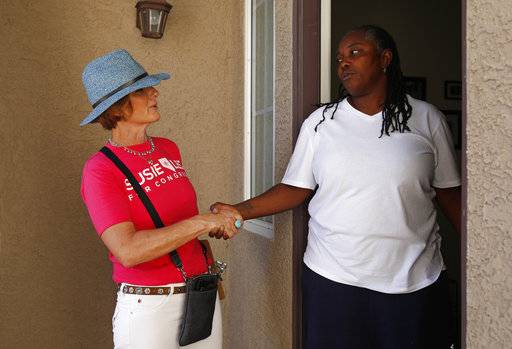 Susie Lee, left, shakes hands with Cathy Bostic while canvassing a neighborhood on the day of the primary election, Tuesday, June 12, 2018, in Henderson, Nev. Lee is a Democratic candidate for Nevada's 3rd Congressional District.